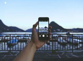 Ein Reise-Blogger nimmt ein atmosphärisches Foto von einem italienischen Hafen mit dem Iphone auf