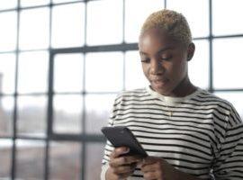 Eine Frau checkt ihren Instagram Newsfeed auf dem Iphone und ist begeistern von den Fotobeiträgen Ihres Lieblingshotels