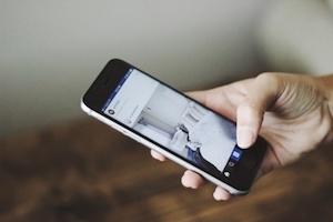Eine Frau scrollt durch ihren Instagram Newsfeed und ist begeistert durch die Beiträge Ihrer abonnierten und favoristierten Destinationen, Hotels, Museen und Events