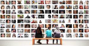 Besucher sitzen in einer Fotoausstellung vor einem großen Foto-Collage