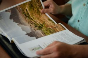 Eine Frau liest in einem Reisemagazin, dabei wird ihre Aufmerksamkeit für eine touristische Destination durch Print Tourismus-Werbung gewonnen