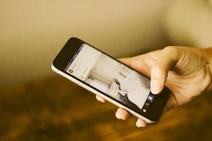 Eine Frau scrollt durch ihren Instagram Newsfeed und wird durch den Foto-Beitrag eines Museum zum Kauf eines Ausstellungsticket motiviert